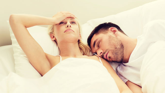 unhappy woman having sleepless night with sleeping and snoring man