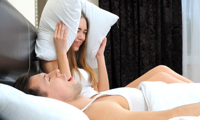 young couple holding pillow on the ears because of snoring boyfriend