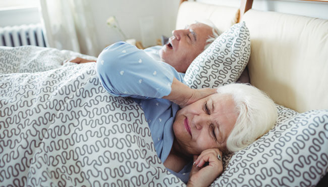 Man snoring and woman covering her ears