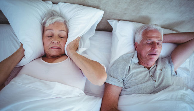 senior woman blocking ears with pillow while husband snoring